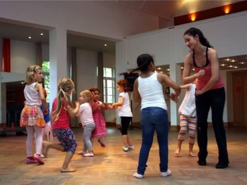 Tanzende Kinder mit einer Tanzlehrerin.