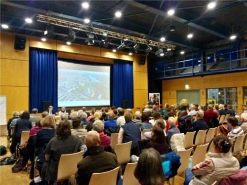 In einem großen Saal sitzen viele interessierte Einwohnerinnen und Einwohner. Am Rednerpult steht Oberbürgermeister Schostok.