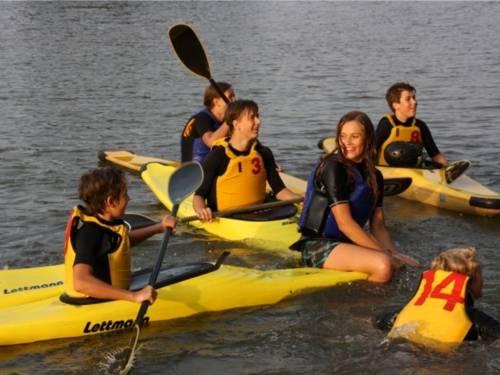 Jugendliche KanufahrerInnen auf einem Gewässer.
