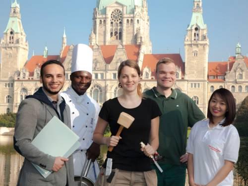 Azubis (drei Männer, zwei Frauen) verschiedener Berufsgruppen stehen zusammen vor dem Hannoverschen Rathaus - zum Teil mit Arbeitsutensilien
