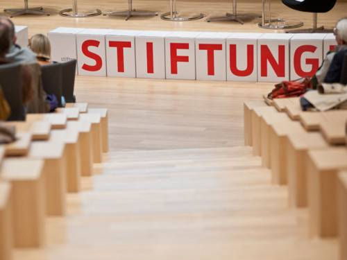 """Blick aus dem Auditorium auf den Schriftzug """"Stiftungen"""" vor einer Bühne"""