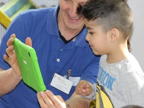 Ein städtischer Mitarbeiter zeigt einem interessierten Jungen den Umgang mit einem Tablet.