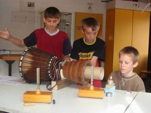 Drei Schüler experimentieren mit der Flamme einer Kerze
