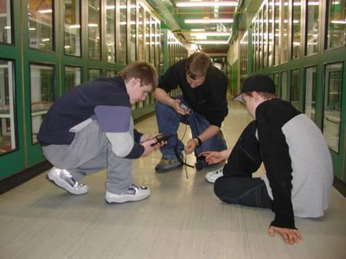 Drei Schüler messen in einem hell erleuchteten Korridor die Lichtstärke