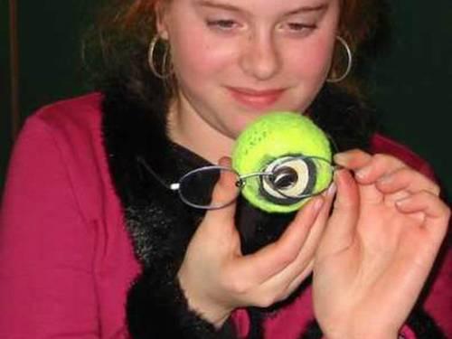 Eine Schülerin hält eine Brille vor das erstellte Augenmodell in Form eines Tennisballs