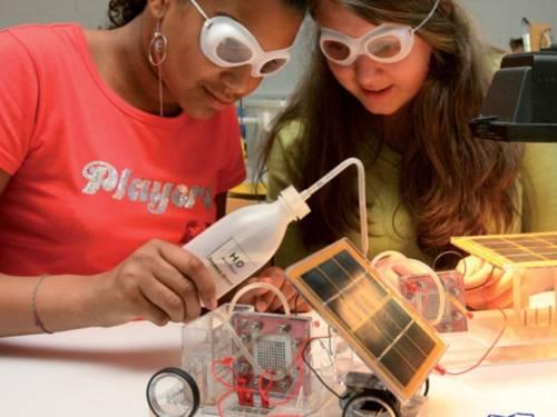 Zwei Schülerinnen mit Schutzbrillen arbeiten mit einem kleinem Solarmobil