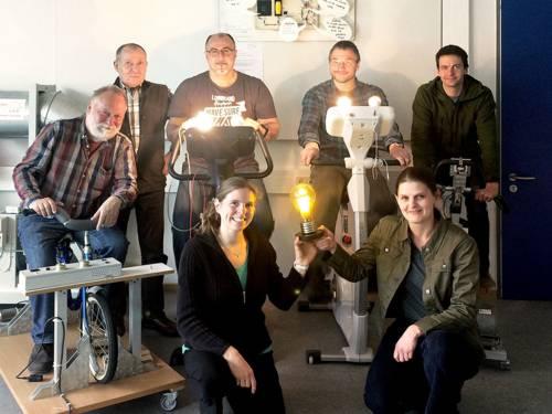 Gruppenaufnahme: Vier Herren im Hintergrund radeln auf Fahrrädern zur Stromerzeugung, ein Herr steht daneben, im Vordergrund zwei Frauen mit einer leuchtenden Glühbirne