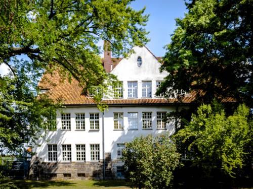 Ein zweigeschossiges, weiß angestrichenes Altbaugebäude mit vielen Fenstern und einem ausgebauten Dachgiebel.