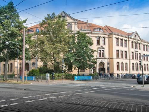 Die Schule Auf dem Loh ist ein dreistöckiges historisches Gebäude mit hohen Räumen und Ziegeldach in der Nähe einer Straßenkreuzung, die mit einem Gitter gesichert ist