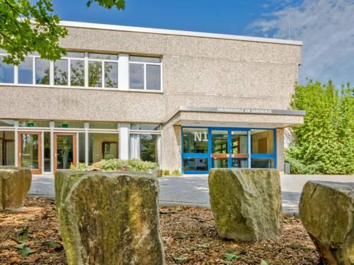 Der Eingang zur Grundschule am Sandberge mit blauen Türen in einem zweistöckigen Gebäude mit großen Fensterfronten und Waschbetonverkleidung.