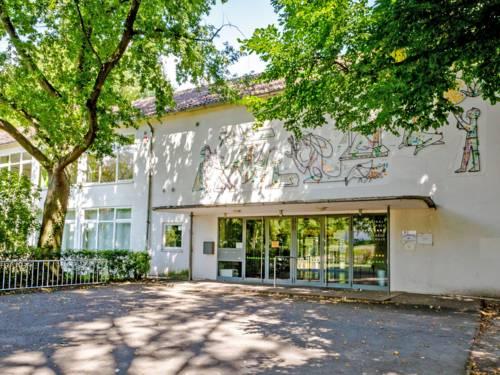Eingang zur Pestalozzi Grundschule - ein zweistöckiges Gebäude, über dessen Eingangsdach bunte Figuren im 60er-Jahre-Stil zu sehen sind.