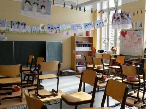 Blick in ein Klassenzimmer, das mit den Zeichnungen von Schülerinnen und Schülern geschmückt ist