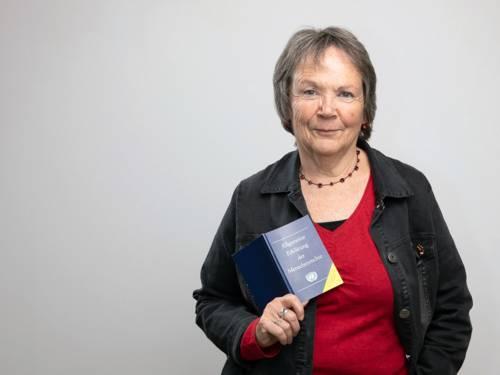 """Eine Frau lächelt und hält ein Buch mit dem Titel """"Allgemeine Eklärung der Menschenrechte"""" in die Kamera."""