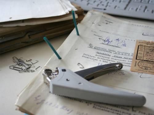 Bei der sorgfältigen Umverpackung der Akten werden die Dokumente von schädlichen Metall-Heftklammern befreit.
