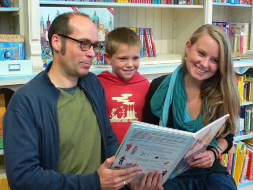 Ein Mann, ein Junge und eine Frau halten ihr Buch lächelnd in die Kamera.