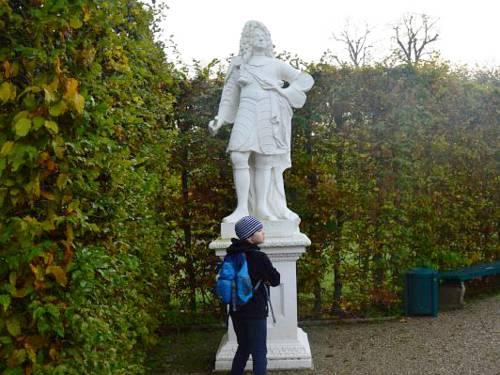 Kind vor Statue