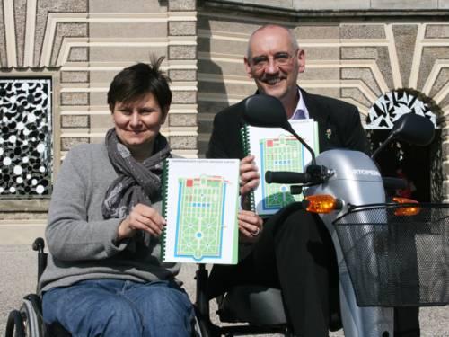 Andrea Hammann, Beauftragte für Menschen mit Behinderung der Landeshauptstadt Hannover, und Gartendirektor Ronald Clark präsentieren die Reliefpläne und die E-Scooter