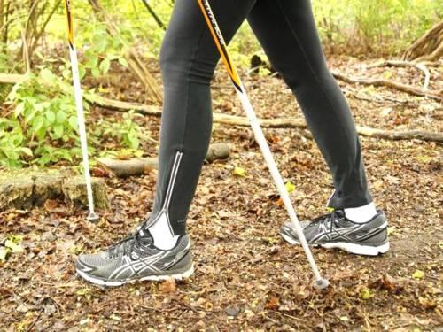 Zu sehen sind zwei Läuferinnenbeine mit Walking-Stöcken