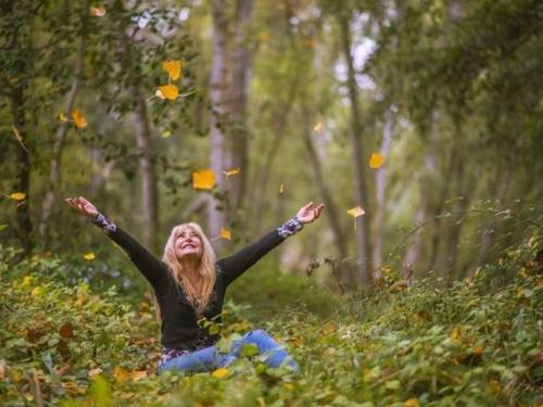 Zu sehen ist eine im Wald sitzende Frau, die bunte Blätter in die Luft wirft
