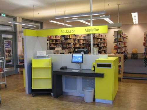 im Vordergrund der Servicebereich der Bibliothek, im Hintergrund Regale mit Büchern