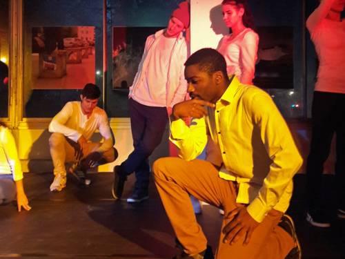 Mehrere Jugendliche in unterschiedlichen Posen auf einer Bühne