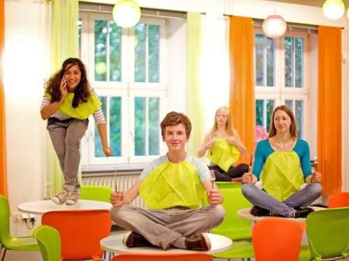 Drei Jugendliche mit Serviette im Ausschnitt und Messer und Gabel in den Händen sitzen im Schneidersitz auf kleinen Tischen im Gastronomiebereich des Haus der Jugend; eine Jugendliche tanzt mit Handy am Ohr auf einem Tisch.