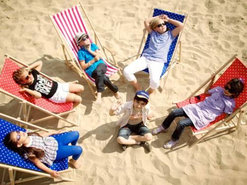 Kinder im Sand auf Liegestühlen