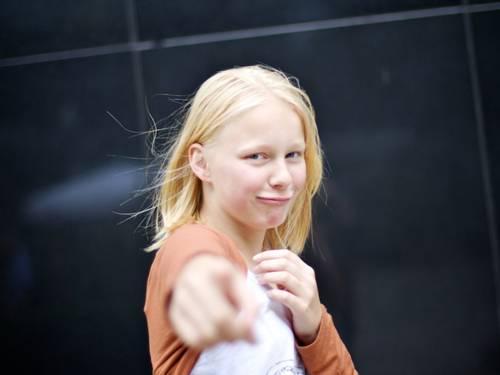 Jugendliche zeigt mit der Hand auf die betrachtende Person