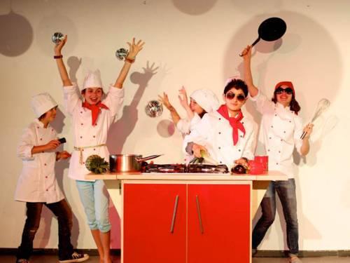 Kinder jonglieren mit Küchengeräten und Gemüse