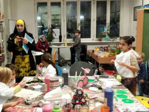 Kinder basteln an einem Tisch, im Hintergrund zwei erwachsene Frauen, die sich mit den Kindern beschäftigen.