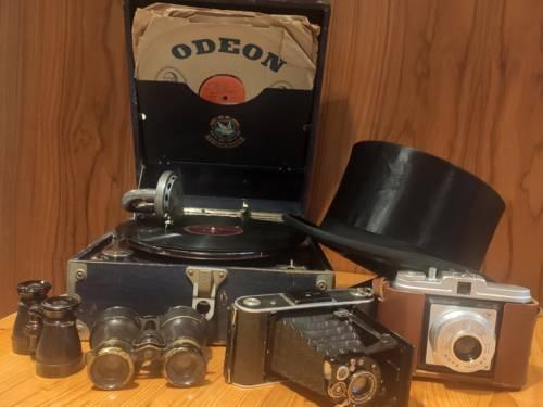 Fotoapparate mit Zubehör, Koffergrammofon mit Schallplatten und Chapeau Claque.