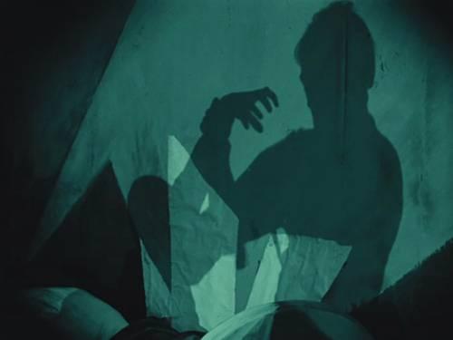 Das in grün gehaltene Bild zeigt einen Schatten an der Wand. Dieser hat einen Arm erhoben und die Finger der Hand gespreizt