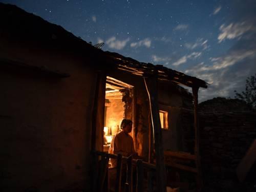 Im Bild zu sehen ist eine Frau, die nachts in der Tür eines ärmlichen Steinhauses gedankenverloren sitzt.