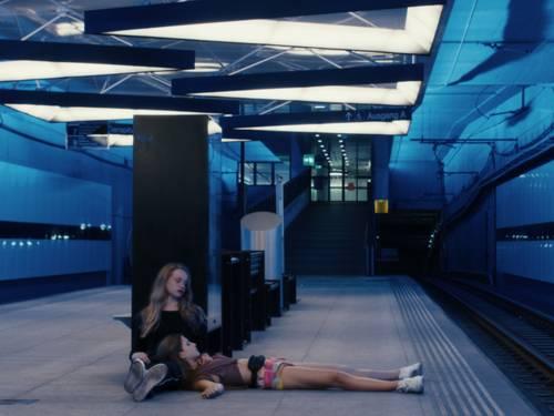 Zwei Mädchen sitzen/liegen betrunken an einer leeren U-Bahn-Haltestelle.