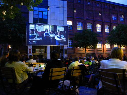 Menschen, die an Tischen sitzen und unter freiem Himmel eine Kinovorführung verfolgen.