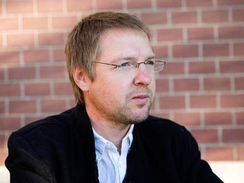 Portrait von Christian Lehnert vor einer roten Backsteinwand