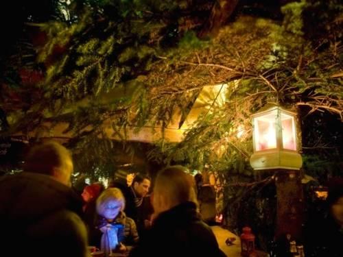 Eine Laterne beleuchtet eine Tanne im Wunschbrunnenwald, unter der ein Holzstand aufgebaut ist.
