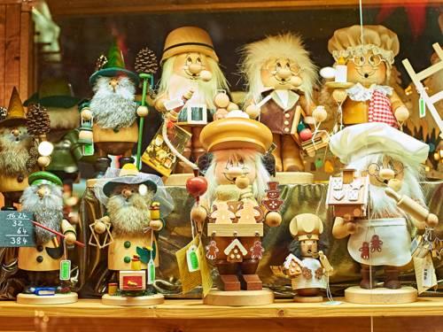 Holzfiguren und Wichtelmännchen, die auf dem Weihnachtsmarkt an einem Verkaufsstand präsentiert werden