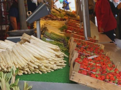 Auf einem Wochenmarktstand liegen Spargelstangen (weiß und grün), Rhabarber und Erdbeeren.