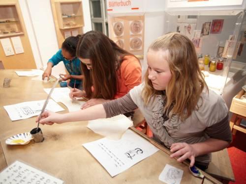 Jugendliche sitzen an einem Tisch und schreiben mit der Tintenfeder