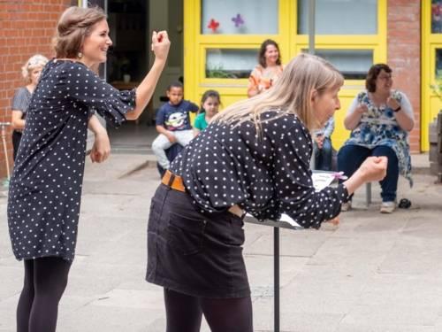 Zwei Frauen, die vor Publikum spielen.