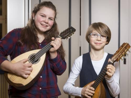 Ein Mädchen mit einer Mandoline, neben einem Jungen mit Mandoline.