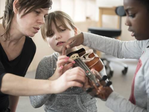 Zwei Mädchen und eine Frau mit einer Geige.