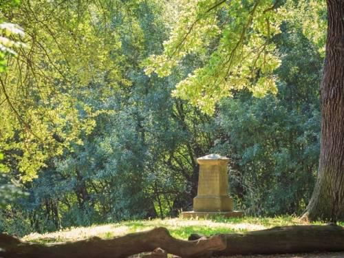 Auf einer Rasenfläche im Hinüberschen Landschaftspark steht eine Stele umrahmt von alten Bäumen