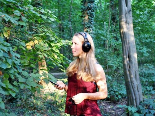 Junge Frau mit Kopfhörern im Wald