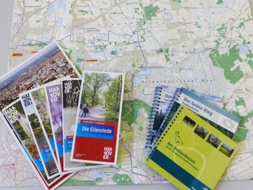 Broschüren und Kartenmaterial sind auf einer Landkarte ausgebreitet