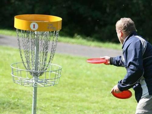 Ein Mann visiert einen Discgolf-Zielkorb an
