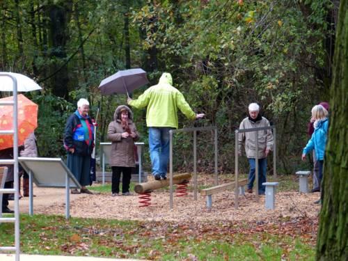 Eine Person mit Regenschirm balanciert auf einem Holzstamm im Bewegungspark in Stöcken