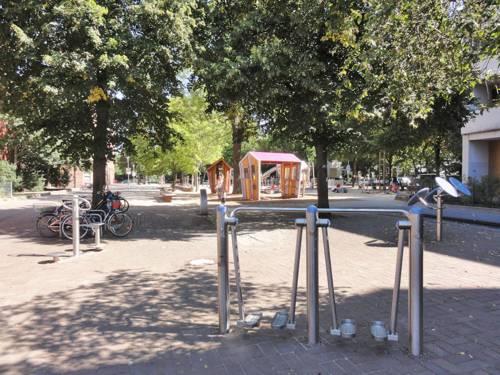 Im Vordergrund Beintrainer, im Hintergrund weitere Geräte des Fitnessparcours an der Velvetstraße