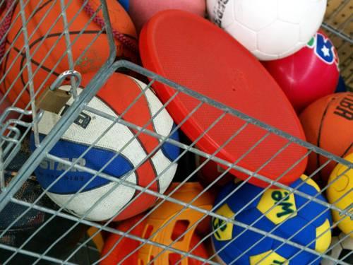 Ein Gitterkorb aus Metall mit einer Frisbee und verschiedenen Bällen, u.a. Basketbälle und Fußbälle